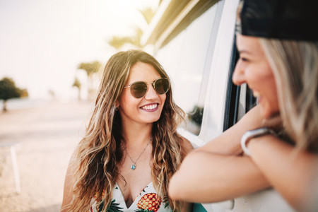 Two young women smiling in a camper van