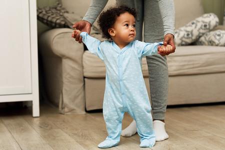 Mother teaching baby boy to walk
