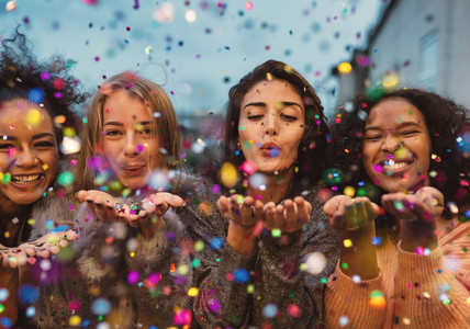 Young women blowing confetti