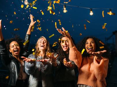 Happy women throwing confetti