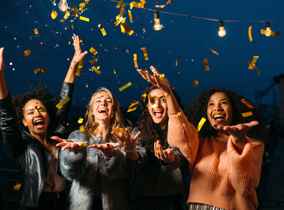 Happy women throwing confetti