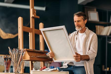 Senior painter sitting in studio