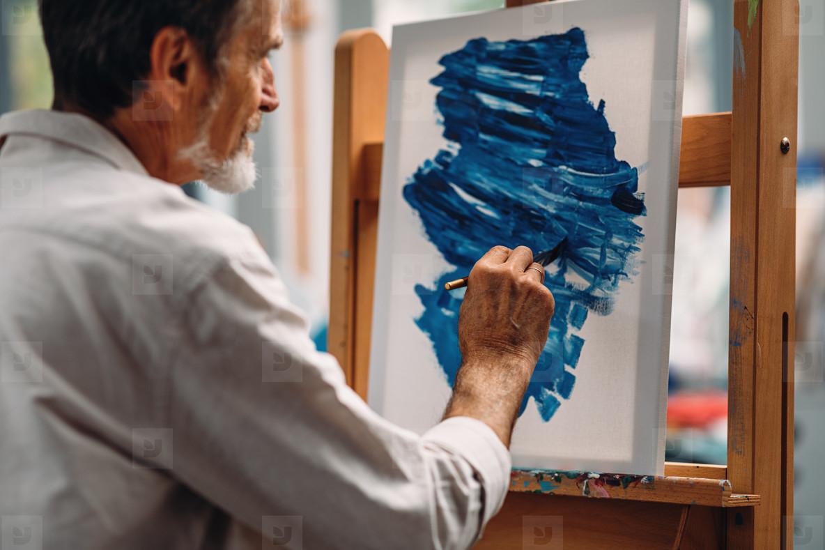 Senior painter drawing on canvas
