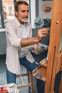 Bearded artist sitting indoors
