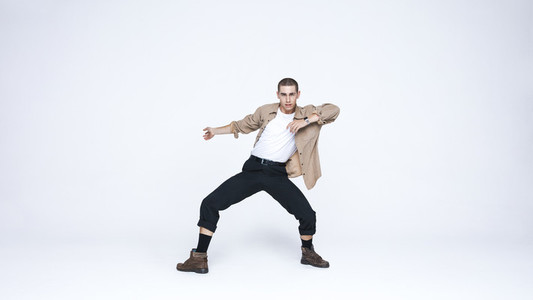 Young man dancing against white background