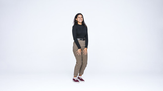 Smiling young woman standing on white background