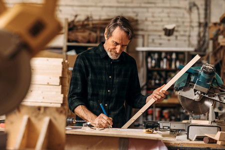 Senior carpenter holding a plank