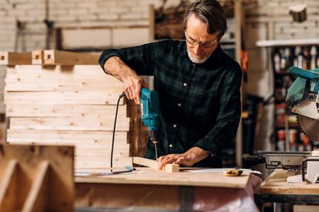 Carpenter using electric drill