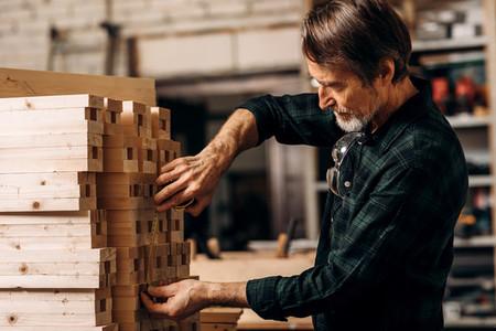 Senior carpenter using measuring