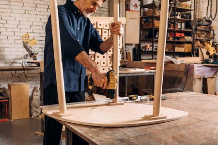 Senior male carpenter drilling