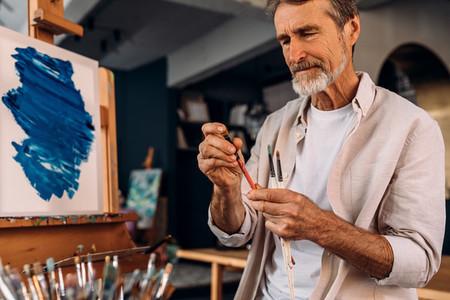 Mature painter checking brush