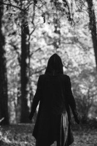 View from the back on a black witch in a mantle during ritual in a forest  Black and white moody photography  The concept of Halloween and witchcraft