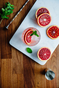 Refreshing cold summer cocktail with blood orange and mint on a marble tray Top view flat lay composition copy space