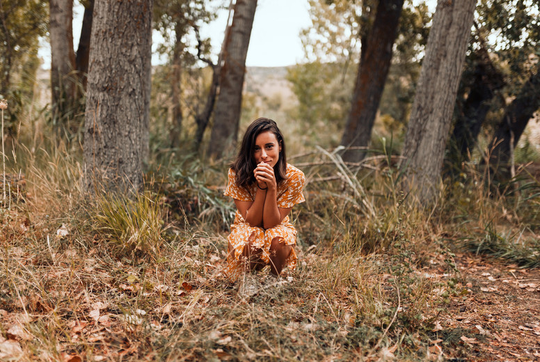 Young smiling woman squatting in the forest wearing a dress