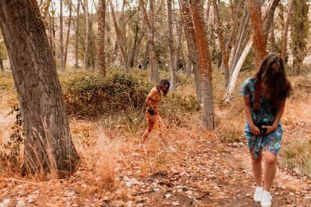 Two young women walking through the forest wearing dresses