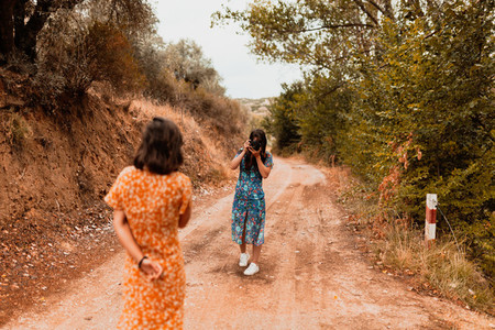 Two young women taking photos on a path near a forest