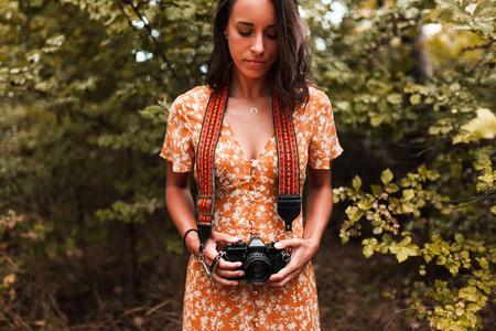 Young woman with analog camera wearing a dress in the forest
