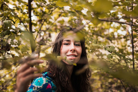 Young smiling woman wearing dress in the forest