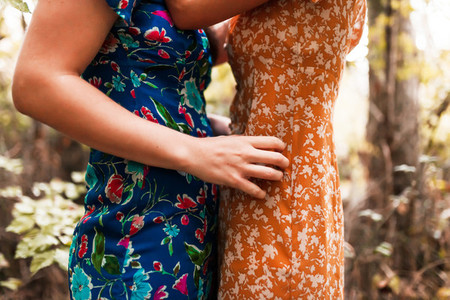 Two hugged women surrounded by forest plants