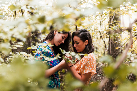 Two women touching their hands surrounded by forest plants