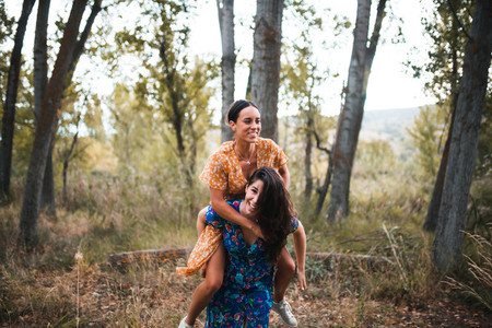 Woman piggybacking happy girlfriend while enjoying on the forest