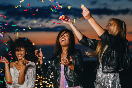 Laughing women throwing confetti