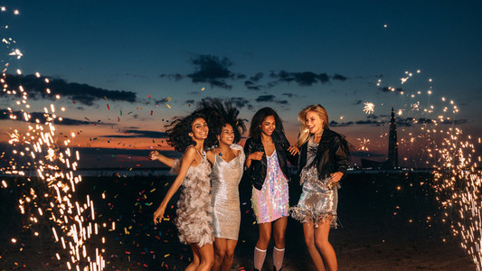 Four women celebrating at sunset