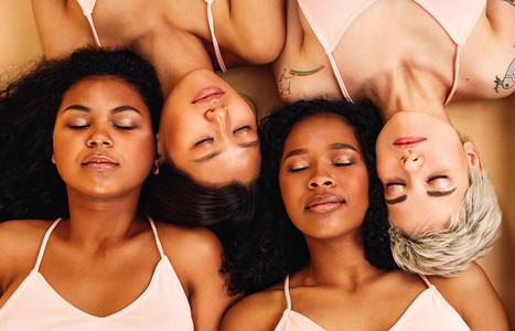 Four diverse women lying on back