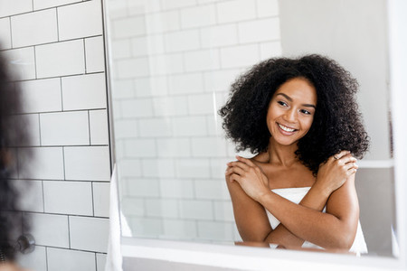 Happy woman looking at mirror