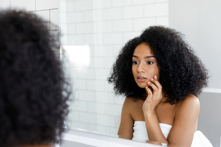 A young woman looking at mirror