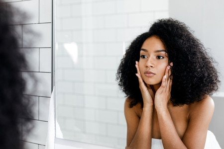 Mixed race woman massaging face