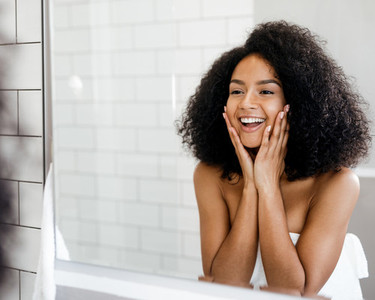 Happy woman admiring her skin