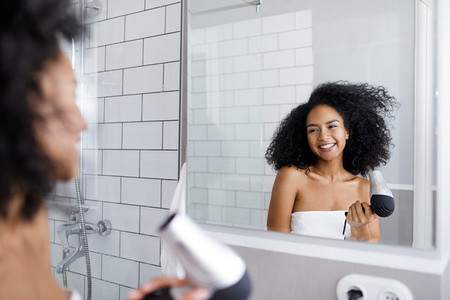 Smiling woman holding a hair dry