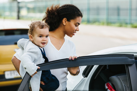 Young mother opening a car door