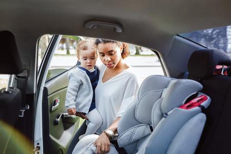 Young parent adjusting baby seat