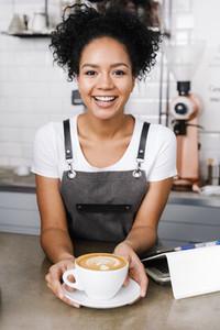 Woman barista in her coffee shop