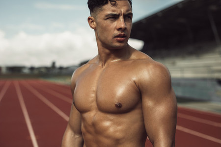 Muscular man relaxing after exercise on track field
