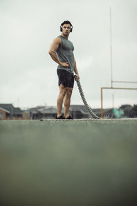 Sportsman taking break from battling rope workout