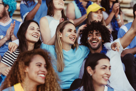 Happy Argentinian soccer fans watching a match in stadium