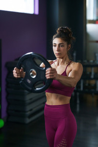 Athletic woman doing triceps push ups with a barbell plate