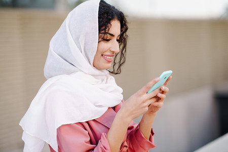 Young Muslim woman wearing hijab texting message with her smartphone