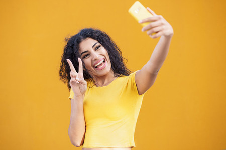 Young Arab woman taking selfie photograph with smartphone