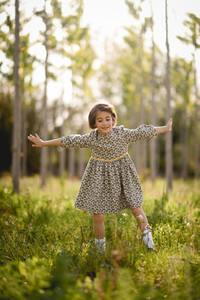 Little girl in nature field wearing beautiful dress
