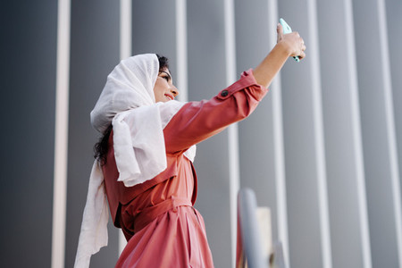 Arab Woman with hijab taking selfie with smartphone