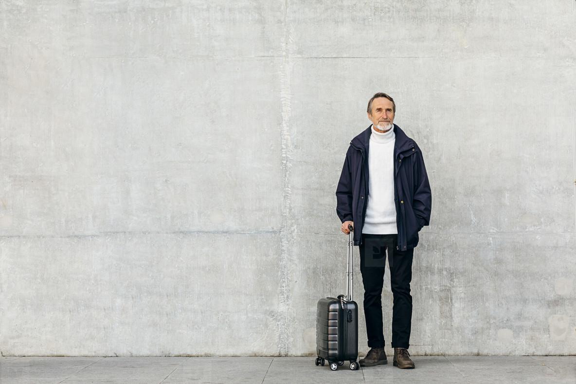 Senior tourist standing at wall