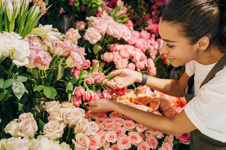 Smiling woman looking on flowers