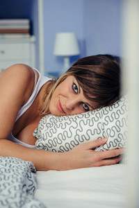 Young woman lying on the bed looking at camera