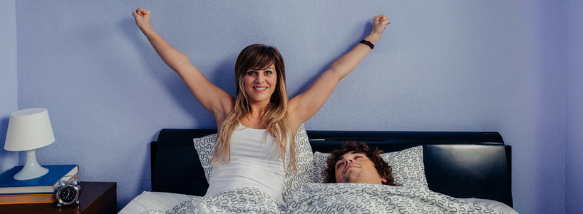 Woman waking up and husband sleeps