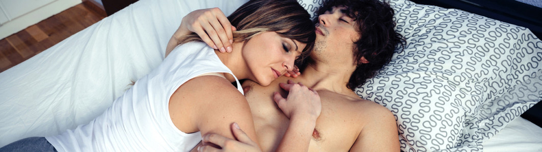 Young couple in love embracing lying over a bed