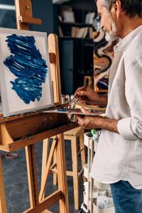 Senior painter standing